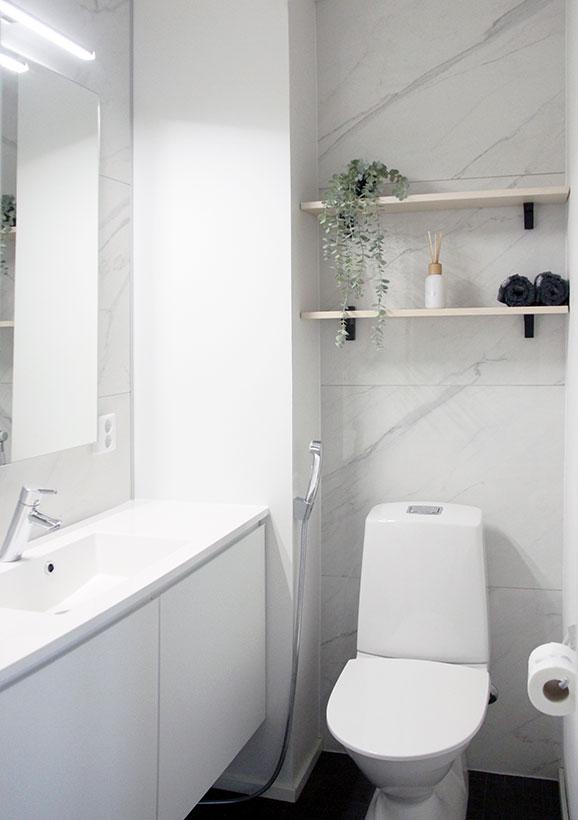 Hento marmorikuvio ja vaalea puu tuovat hienostuneen tunnelman vaaleaan wc-tilaan